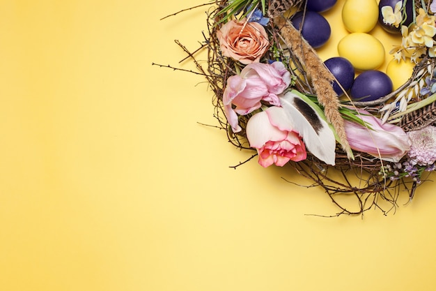 Painted easter eggs in nest on yellow table background. top view of easter decoration. happy easter concept. trendy colors
