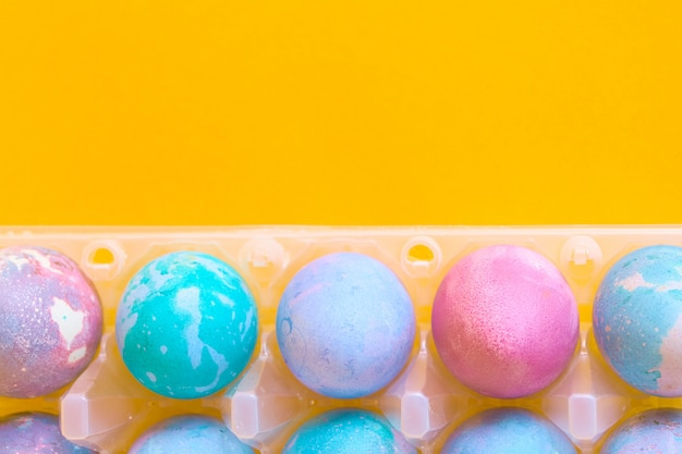 Painted easter eggs with space intergalactic pattern in stand on yellow background