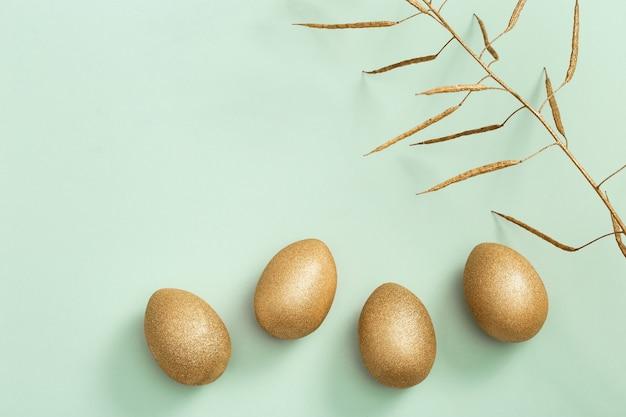 Раскрашенные пасхальные блестящие яйца и золотые цветы. минимальная концепция пасхи.