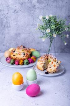 Расписные яйца и краффин (cruffin) с изюмом, орехами и цукатами. хлеб пасхальный кулич. пасха.