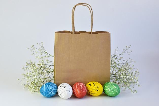 색칠 한 달걀과 꽃은 종이 봉지 옆에 놓여 있습니다. 부활절에 배달. 공간의 사본. 광고 브랜딩.