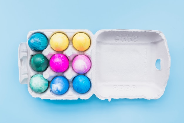 Painted eggs in carton box on blue background