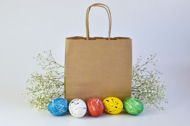 Painted eggs and flowers lie next to a paper bag. delivery on easter. a copy of the space. advertising branding.