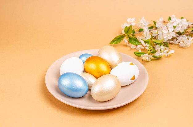 コピースペースのあるベージュの背景のプレートにイースターの卵を描いた。季節性のコンセプト、春、はがき、休日。フラットレイ、テキストの場所。閉じる。