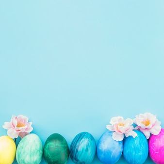 Painted eggs with flowers on blue background