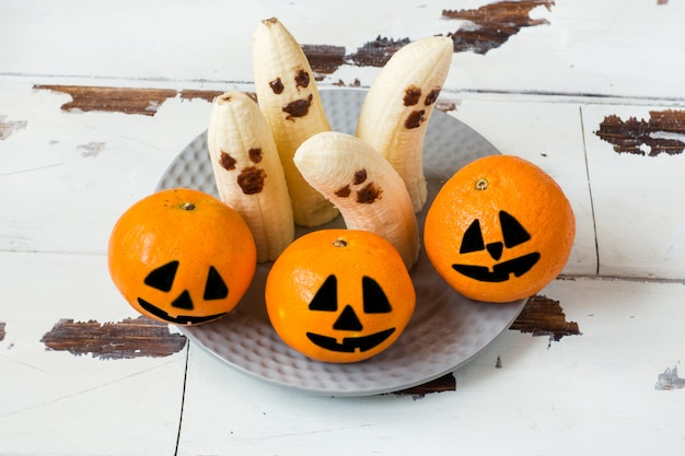 Painted funny faces on tangerines and bananas for halloween