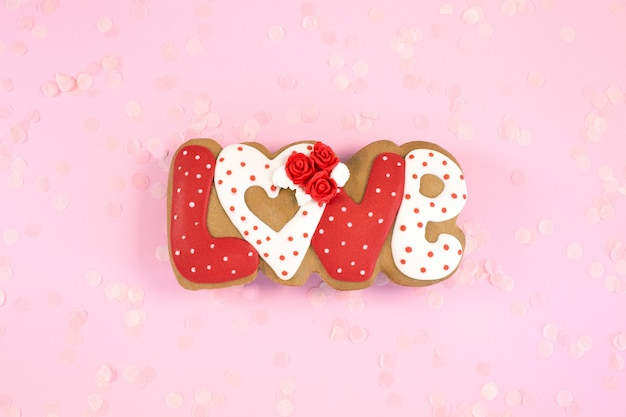 Painted gingerbread cookies in shape of word love on a pink desk. love romance concept.top view. copy space