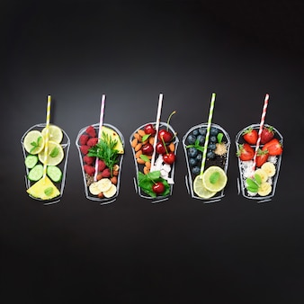 Painted glasses with food ingredients for smoothies, drinks on black chalkboard