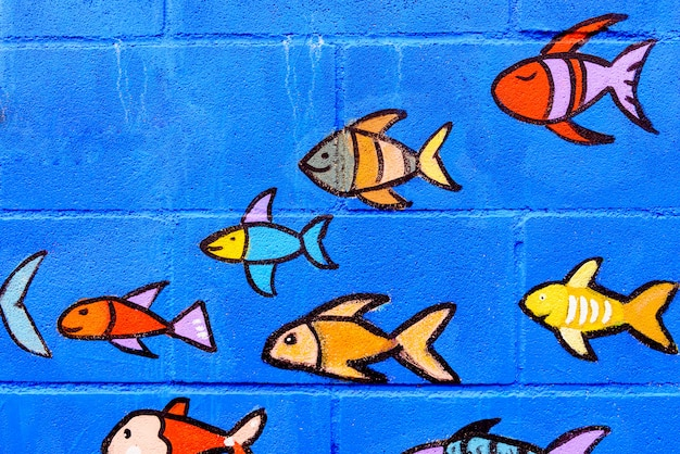 Painted goldfish decorate a blue wall for children.