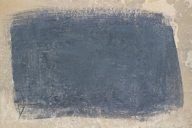 Painted gray rectangle on a beige concrete surface.