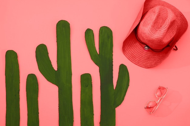 Painted green cactus with hat and sunglasses on coral background