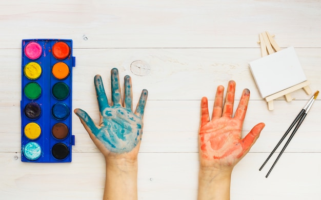 Painted hand and painting supplies on wooden table