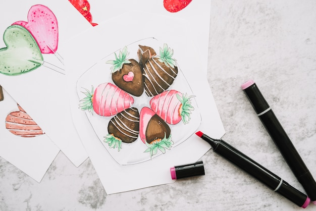 Painted hearts and strawberries on paper near markers