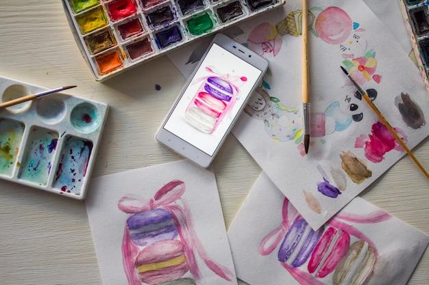 Роспись картин торты акварелью, краски и кисти на виде сверху столешницы.