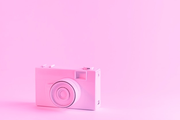 Painted pink camera against pink background