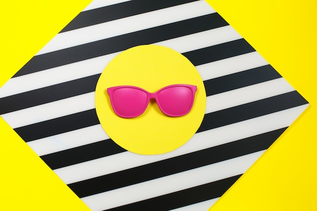 Painted pink fashion sunglasses on colorful background.