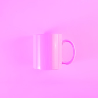 Painted pink mug with handle against colored background