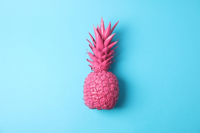 Painted pink pineapple on blue background, space for text