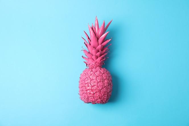 Окрашенный розовый ананас на синем фоне, место для текста