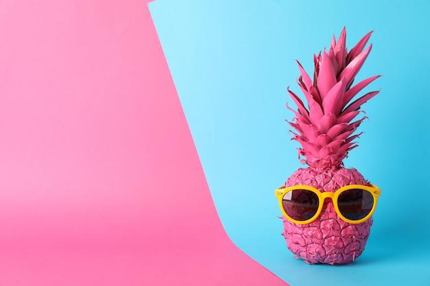 Окрашенный розовый ананас с очками на фоне тонов