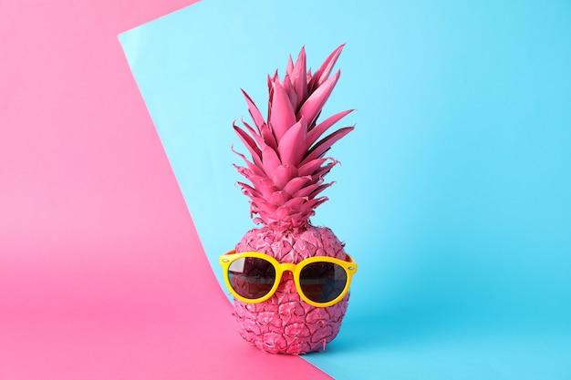 Окрашенный розовый ананас с очками на двухцветном фоне, место для текста