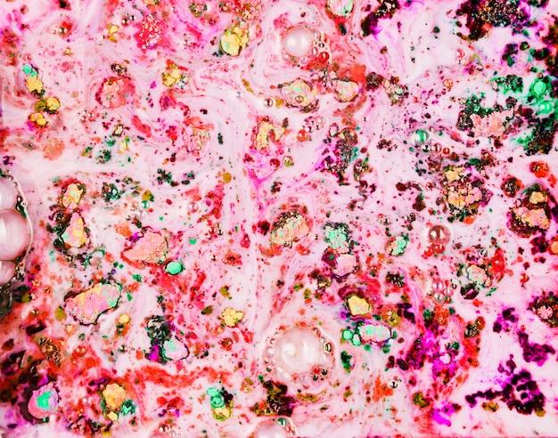 Окрашенный розовый порошок в темной воде