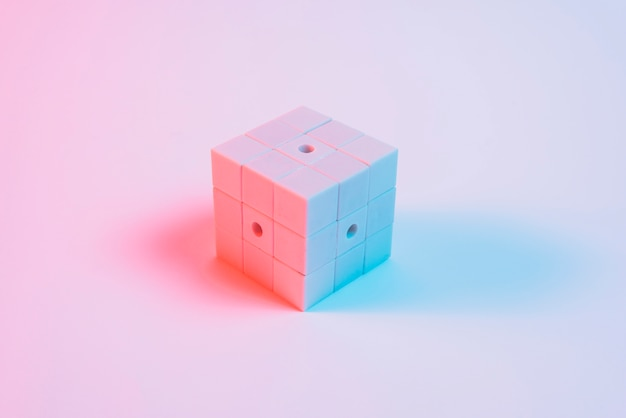 Painted puzzle cube with blue light and shadow against pink backdrop