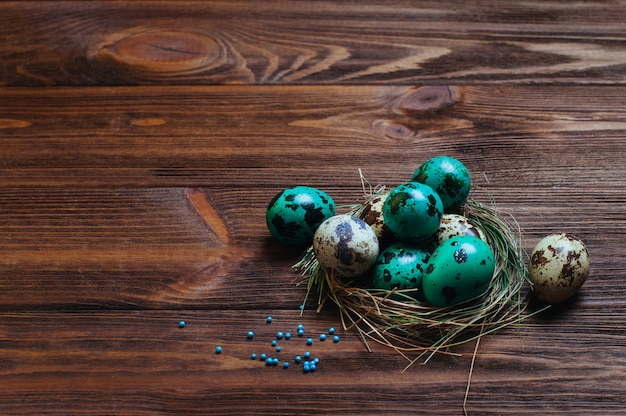 소박한 나무 배경 위에 둥지에 메 추 라 기 달걀을 그린