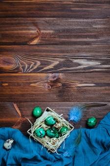 나무 배경 위에 상자에 페인트 메 추 라 기 달걀