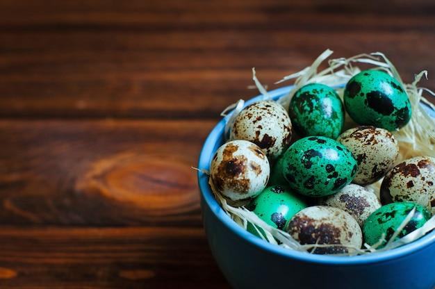 소박한 나무 배경 위에 페인트 메 추 라 기 달걀