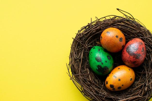 Расписанные красные, оранжевые, желтые, зеленые перепелиные яйца в декоративном гнезде из веточек на желтой поверхности