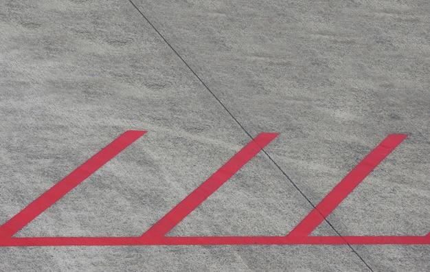 Покрашенная красная линия автостоянки на первом этаже цемента.