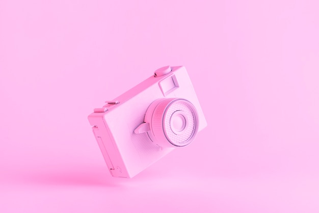 Painted retro camera against pink background
