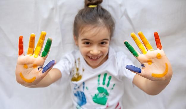 어린 소녀의 손바닥에 그려진 미소. 어린이 손바닥에 재미있는 밝은 그림.
