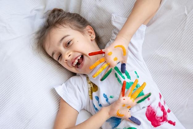 컬러 손바닥이있는 티셔츠에 어린 소녀의 손바닥에 그려진 미소