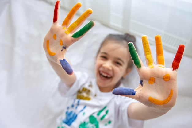Painted smiles on the palms of a little girl. funny bright drawings on children's palms. Free Photo