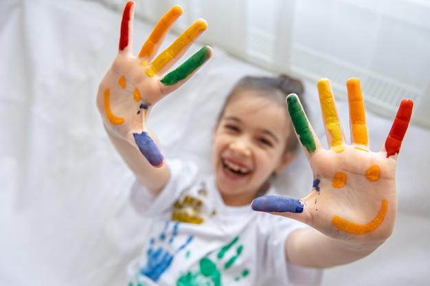 Sorrisi dipinti sui palmi di una bambina. divertenti disegni luminosi sui palmi dei bambini.