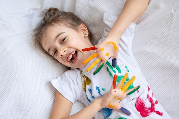 Painted smiles on the palms of a little girl in a t-shirt with colored handprints
