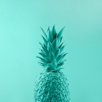 Painted turquoise pineapple on colored backdrop