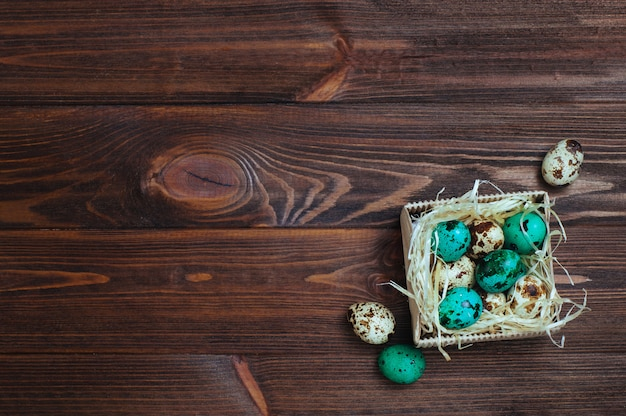 Painted turquoise quail eggs on wooden background