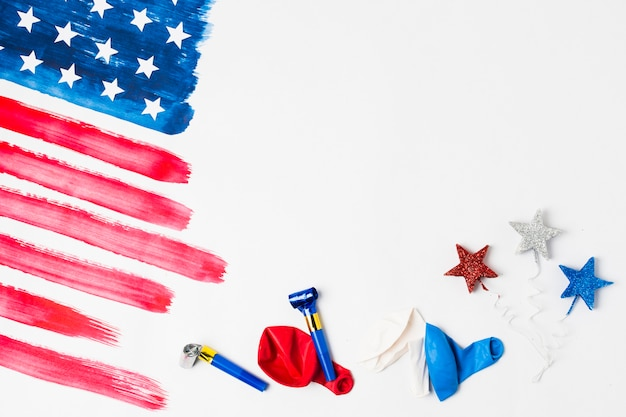 Painted united states american flag with party horn; balloons and star props on white background