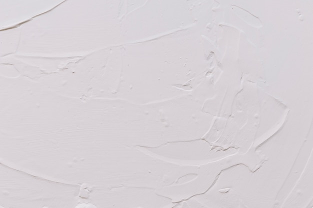 背景のために塗装された白いコンクリートの壁の石膏