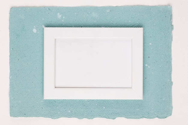Painted white frame on textured paper over white backdrop