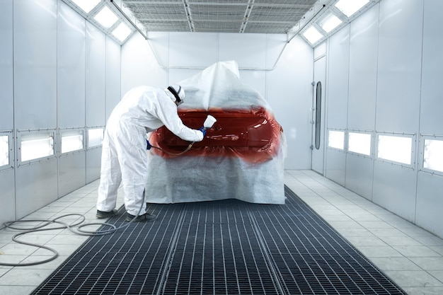 Painter applying new layer of fresh metallic paint on the automobile in painting chamber.