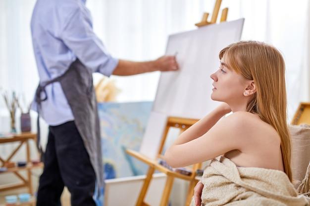 이젤의 화가는 밝은 스튜디오 룸에서 소파에 앉아있는 여성 모델을 그립니다. 예술 개념