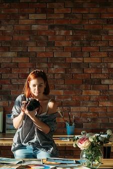 Художник-блогер. рисование и ведение блога. художник женщина фотографирует произведения искусства. скопируйте пространство на кирпичной стене.