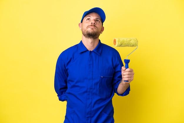 Художник бразильский мужчина, изолированные на желтом фоне и глядя вверх