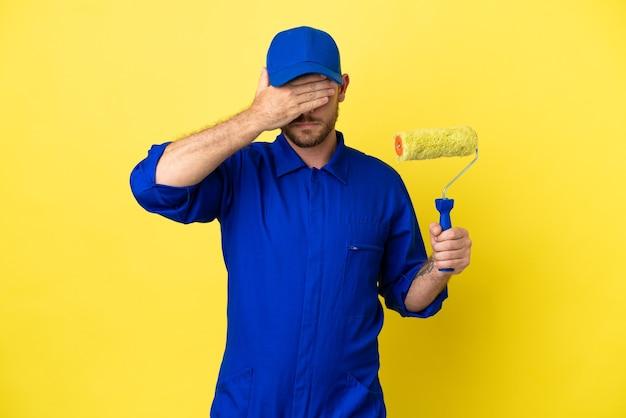Художник бразильский мужчина, изолированные на желтом фоне, закрывая глаза руками. не хочу что-то видеть