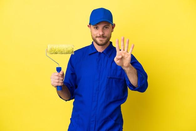 Художник бразильский мужчина изолирован на желтом фоне счастлив и считает четыре пальцами
