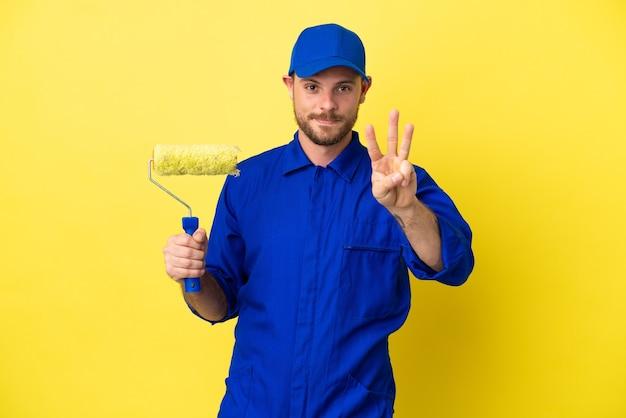 幸せな黄色の背景に分離され、指で3を数える画家ブラジル人